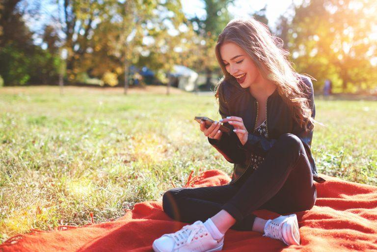 Junge Frau im Park mit Smartphone