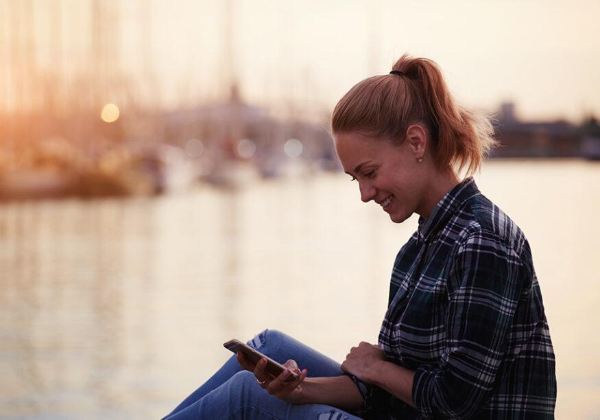 Frau mit Mobile am See