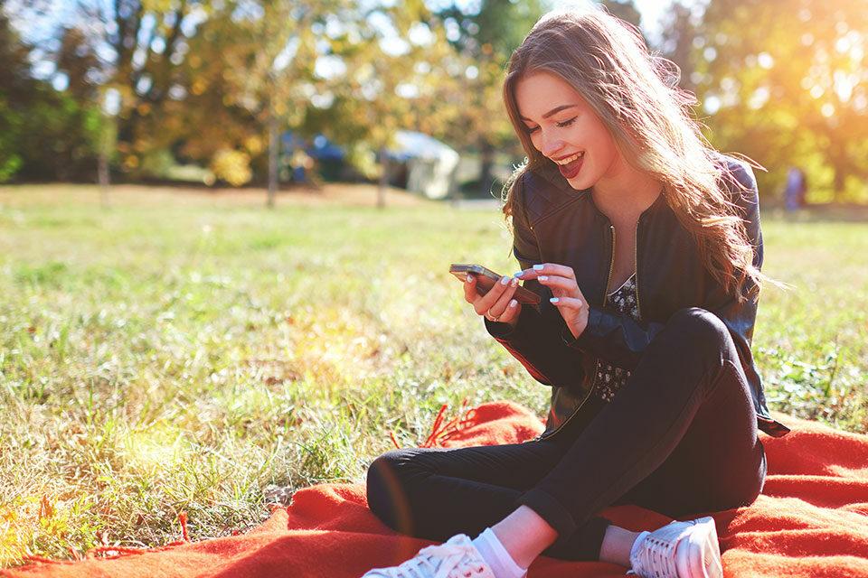 Junge Frau im Park mit Smartphone - mobile
