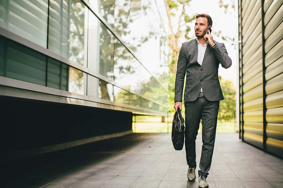 Geschäftsmann unterwegs am Handy Mobile