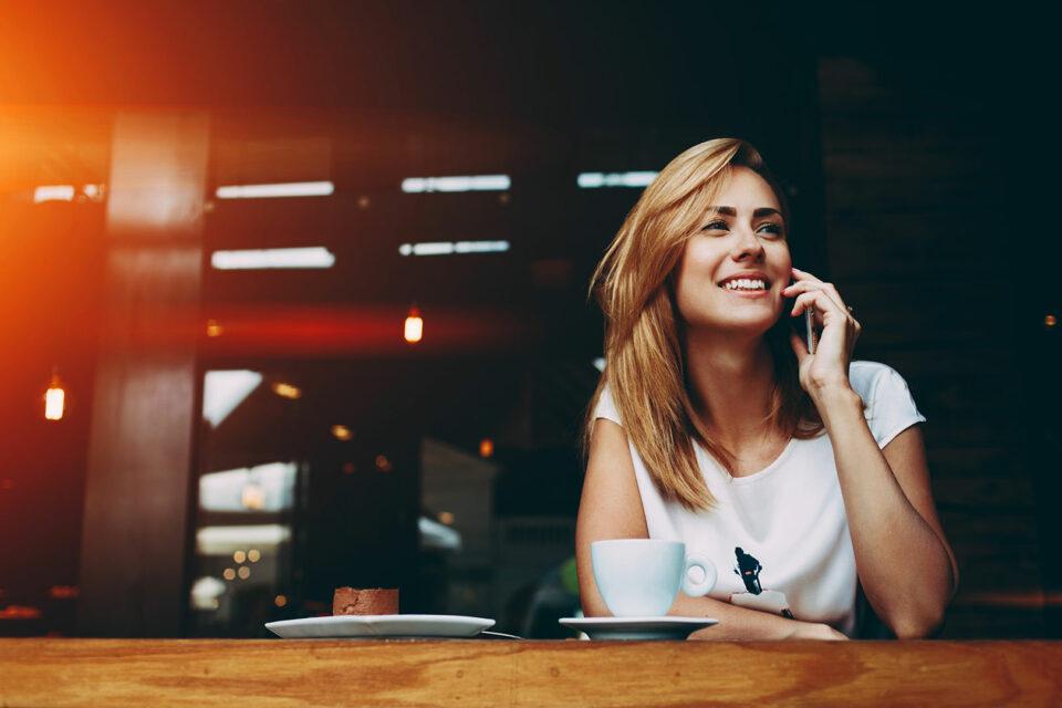 Frau mit Mobile im Kaffee